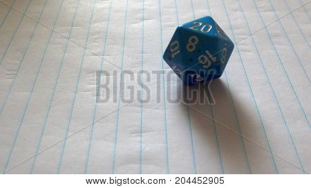 a single blue twenty-sided die with number twenty facing up on lined notebook paper