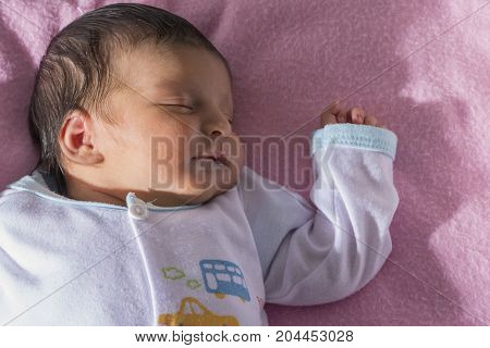 Newborn baby peacefully sleeping on pink blanket