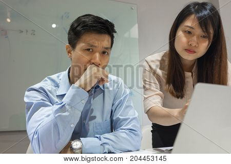 Asian businessman feels annoyed at work by his workmate