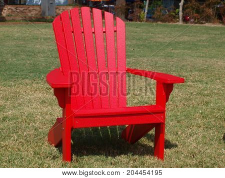 Red Lawn Chair with slat-backs and flat arm rest.