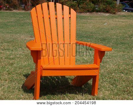 Pumpkin-colored slat-back lawn chair on a grassy lawn.