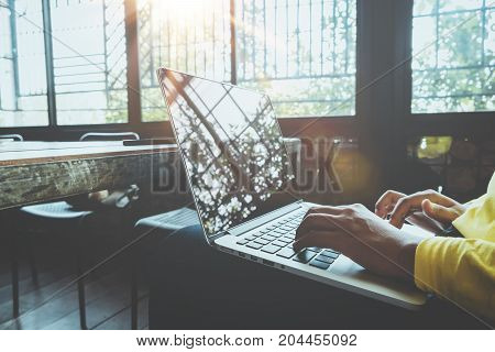 Side view of charming young hipster girl hands working on her laptop sitting at wooden table in a coffee shop. woman using computers in a cafe - vintage color style.