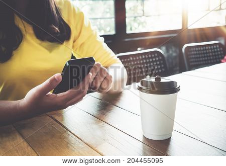 Charming young hipster girl hands using on her smart phone sitting at wooden table in a coffee shop. Asian woman relax sitting in a cafe - vintage color style.