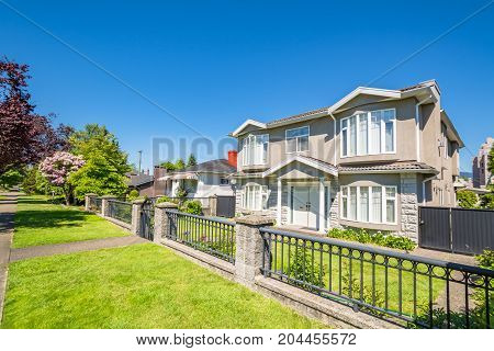 Big residential house with iron fence on the street