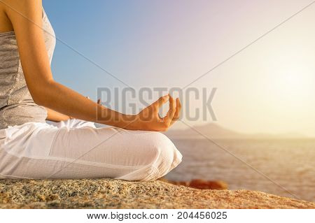 Young Woman Meditation Yoga Pose On Tropical Beach With Sunlight In Background