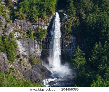 Majestic waterfall flowing down steep mountainous terrain within North Cascades National Park.