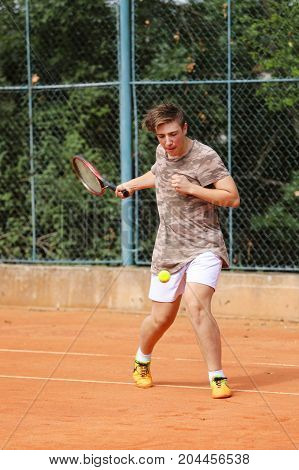 Teenage boy try to play forehand on the tennis court