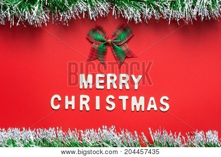 MERRY CHRISTMAS words and ribbon bow on the center of red background with glitter frame on top and bottom