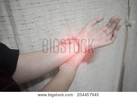 Close up woman holding her wrist symptomatic Office Syndrome Pain symptoms concept.
