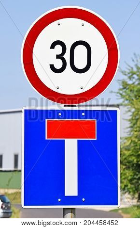 Speed limit and dead end traffic signs on the road