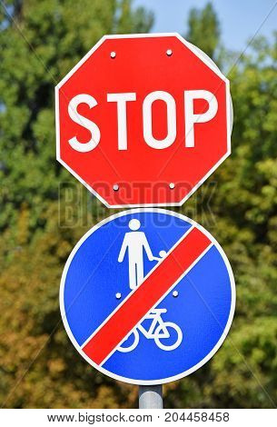 Stop sign and end of bicycle road sign at the road crossing in the city