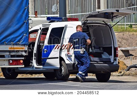 Police man and police car at the scene of a traffic accident