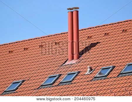 New house roof with smoke stacks against sky