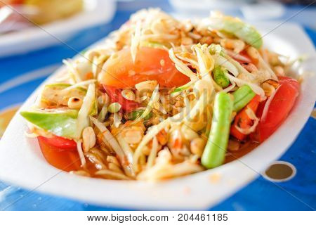 Som Tum Thai or Green Papaya Salad serve on styrofoam plate at Pattaya Thailand.