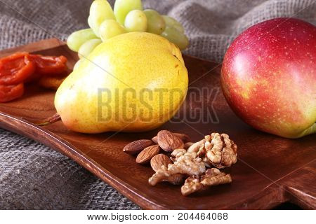 Fresh organic fruits on wood Serving tray. Assorted apple, pear, grapes, dried fruits and nuts