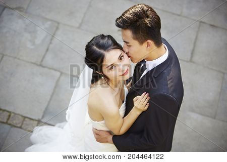 young asian bride and groom embracing kissing dancing in open air high angle view.