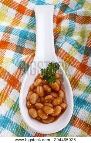 baked beans with parsley served on a white porcelain spoon
