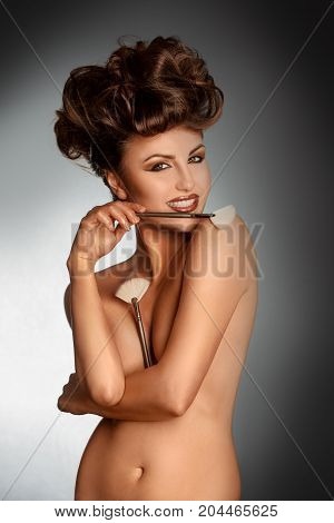 Beauty brunette with cosmetic brushe smiling on camera in studio