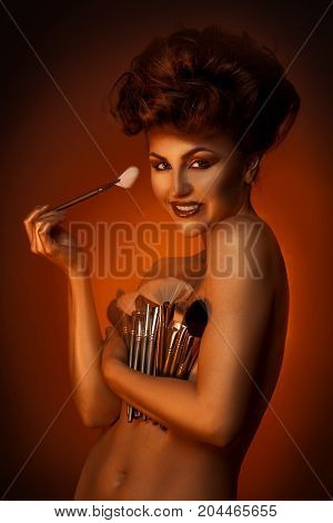 Charming girl smiling at camera with plurality of cosmetic brushes in studio
