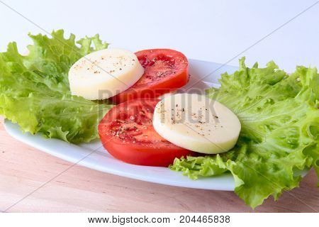 Portion of Mozzarella with Tomatoes, lettuce leaf and Balsamic dressing on white plate. selective focus close-up shot