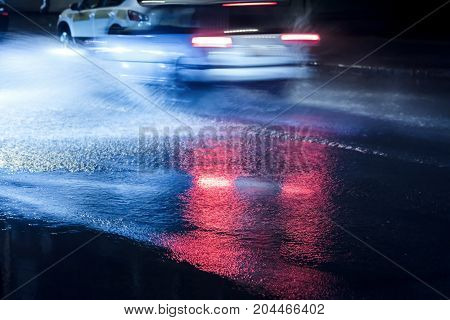 City Traffic Headlights Reflecting In Flooded Road During Rainy Night