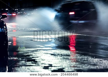 Car In Motion Driving On Wet Flooded Road At Night