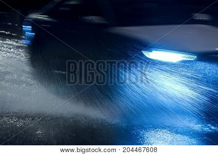 Car Spraying Water As It Drives During Heavy Rain At Night