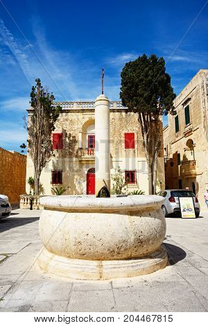 MDINA, MALTA - APRIL 1, 2017 - Stone fountain with a townhouse to the rear in Bastion Square Mdina Malta Europe, April 1, 2017.