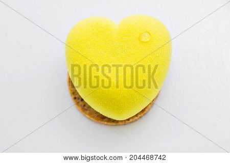 Yellow cake in the shape of heart. lemone desert. white background. this light, airy