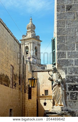 View along a town street towards the Church of the Annunciation of our Lady bell tower with a religious statue in the foreground Mdina Malta Europe
