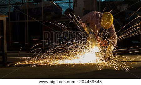 the worker uses cutting machine to cut metal focus on flash light line of sharp sparkin low Light