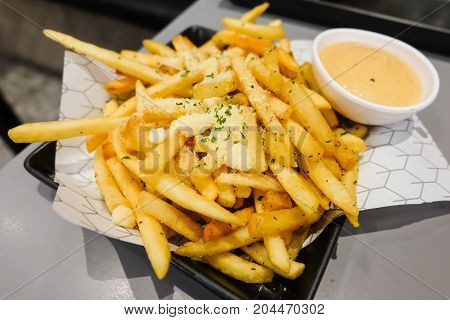 French fries with powder cheese and mayonnaise sauce serve on black plate for food background.