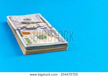 Stack of american dollar bills on the blue background.