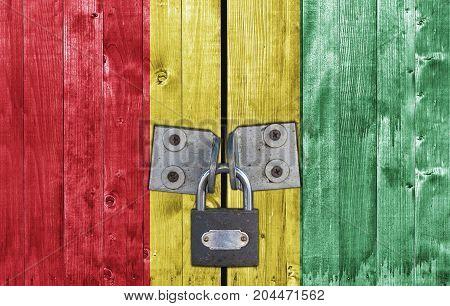 Guinea flag on door with padlock close