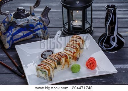 Teapot and sushi set with eel fish souce ginger and wasabi. Nigiri maguro and sushi rolls served on white plate on dark wooden background. Close up view. Rolls derwed with candle and chopsticks