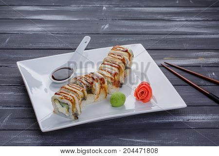 Kanada sushi rolls with salmon eel Philadelphia cheese avocado and cucumber served on white flat plate with chopsticks over blsck background. Asian menu for gourmets in luxury restaurant