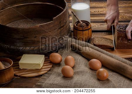 The hand cuts black bread on the background of ingredients for cooking bread. eggs honey milk butter flour sieve rocking chair for dough on a background of burlap and wooden background