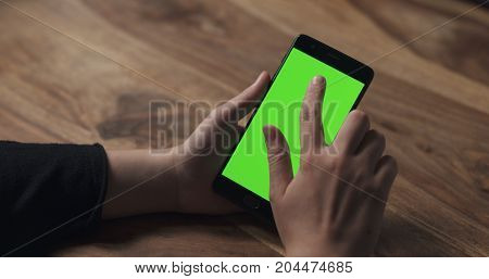female teen girl using smartphone with green screen over wood table, wide photo