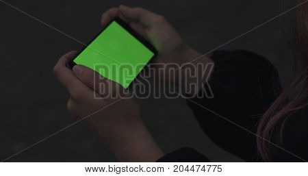 female teen girl holding smartphone with green screen sitting outdoors, wide photo