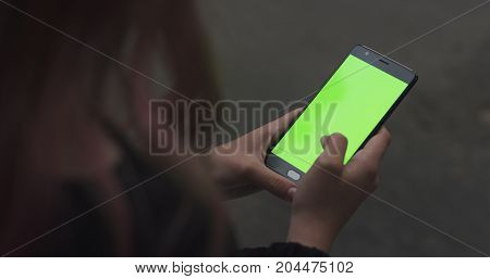 female teen girl using smartphone with green screen sitting outdoors, wide photo