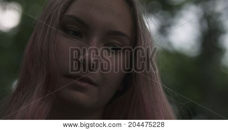 teen girl with purple hair standing in town at night looking at mobile phone, wide photo