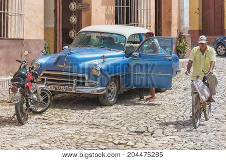 Trinidad,cuba: Senior In Bicycle Passing By An Old American Car