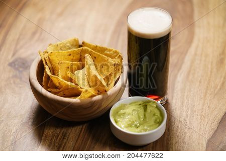 dark beer with nachos and guacamole sauce, shallow focus