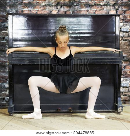 A ballerina and an old piano. Background made of old brick. Music dance education.