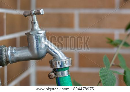 Metal Water Tap With A Green Hose Attached Outside
