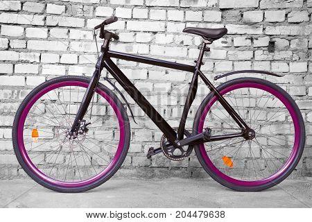 Black Fixed Urban Bike Against Black And White Brick Wall
