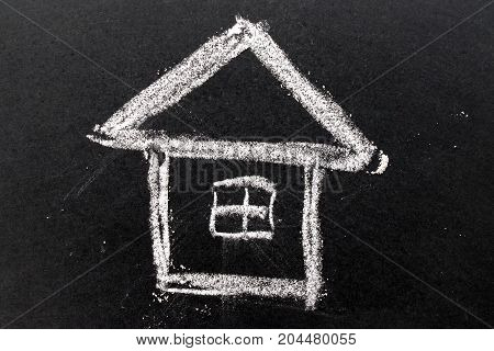 White chalk drawing as house shape on black board background (Concept of dream home happy family)