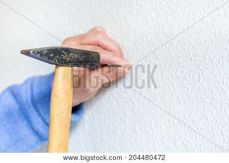 Hammer A Nail Into A White Wall