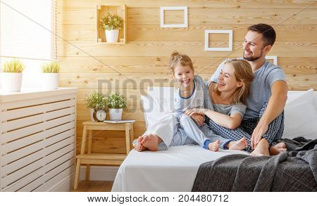 happy family mother father and child daughter laughs in bed