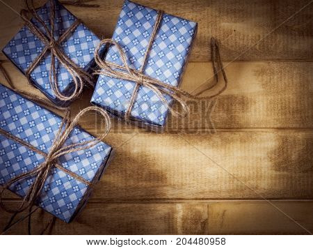 Top view of gift boxes in blue paper decorated with linen cord on the wooden table. Dark toned